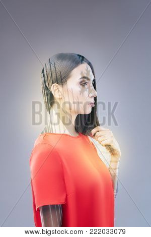I do it. Charming focused serious  woman touching her hair while striving to create  and standing in profile