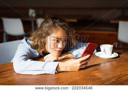 Closeup of thoughtful young Asian woman leaning on table and using red mobile phone at cafe. Student skimming article at coffee shop. Wireless connection concept