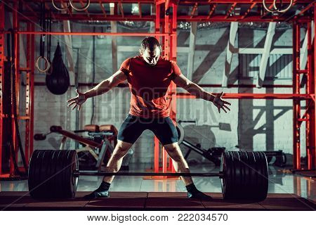Strong muscular man preparing for workout in crossfit gym. Young athlete practicing crossfit training