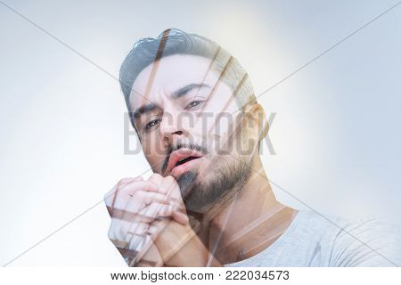 Another future. Handsome worried creative man holding hands together and staring down while reevaluating terms
