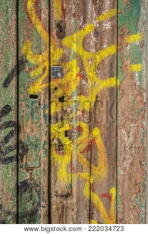 Demaged old wooden door with peeling paint and graffiti