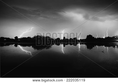 Bolts of lightning over the river. Thunder Sky. Black and white art monochrome photography. Black and white creative photography. Black and white conceptual image. Beautiful black and white background.