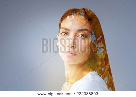 Ideas from nature. Pretty calm wistful woman standing  on the isolated background while desiring new moves  and looking straight