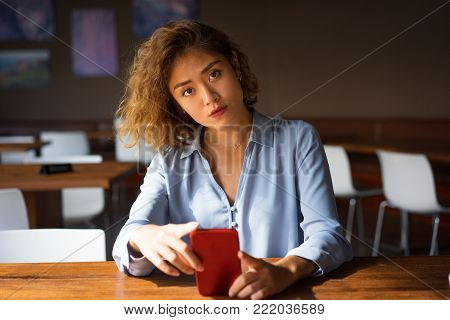 Portrait of thoughtful young Asian woman at cafe holding mobile phone and looking at camera. Young manager surfing Internet during break. Communication concept