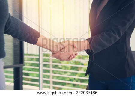 Double Exposure Of Business Handshake And Business People On Deal Concept With City Background