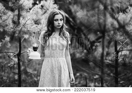 Black and white art monochrome photography. Black and white creative photography. Black and white conceptual image. Beautiful black and white background. Black and white portrait. Very cute young girl with a kerosene lamp.