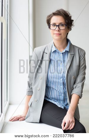 Serene young businesswoman in formalwear sitting on window-sill by office window and looking at camera