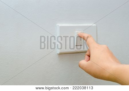 Save electricity Close up of finger is turning on or off on light switch. womans hand with finger on light switch Copy space.
