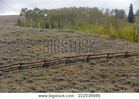 wood rail fence on Wyoming hillside with sagebrush