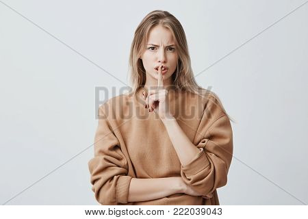 Blonde attractive european female looks at camera keeps finger on lips, being displeased and asks not to make noise, poses in studio. Horizontal shot of good-looking woman, frowning face, making hush gesture