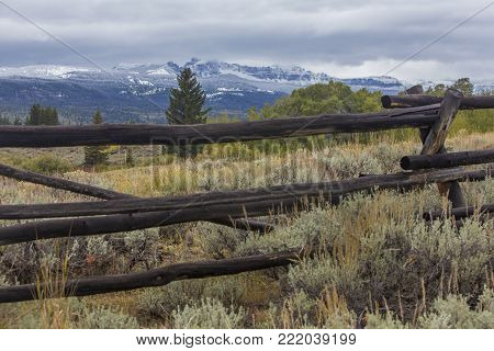 wood rail fence through sagebrush in Wyoming; snow on mountains