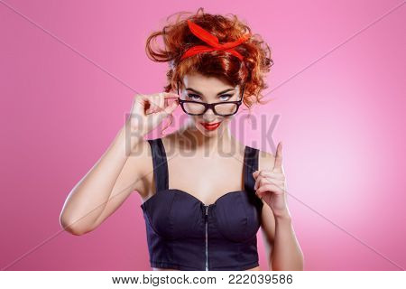 Portrait of a smart pretty girl wearing in glasses over pink background. Pin-up style. Fashion studio shot.