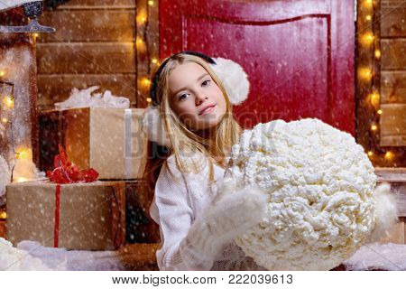Pretty child girl is sitting on the porch of a house decorated for Christmas and holding a big snowball. Time for miracles.
