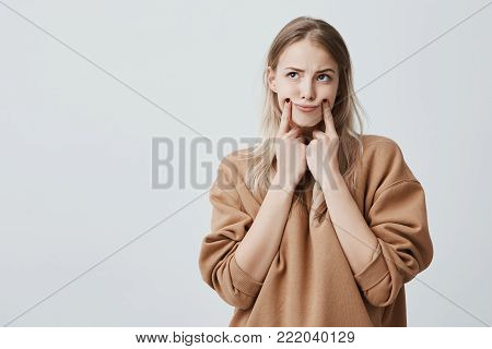 Indoor shot of pretty blonde woman making grimace, touching her cheeks with fingers, looking upwards, having displeased expression. Face expression and negative emotions