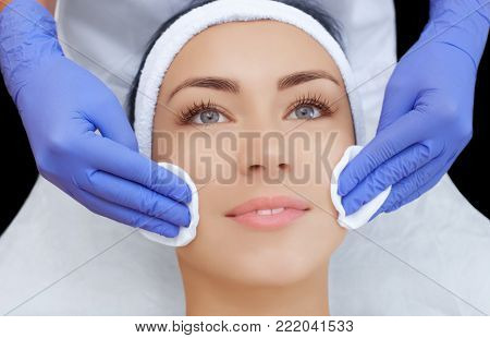 The doctor cosmetologist cleanses with a tonic the face skin of a beautiful, young woman in a beauty salon.Cosmetology skin care. poster