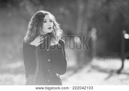 A woman with curly hair in a black coat at the autumn background. Black and white art monochrome photography. Black and white creative photography. Black and white conceptual image. Beautiful black and white background. Black and white portrait.