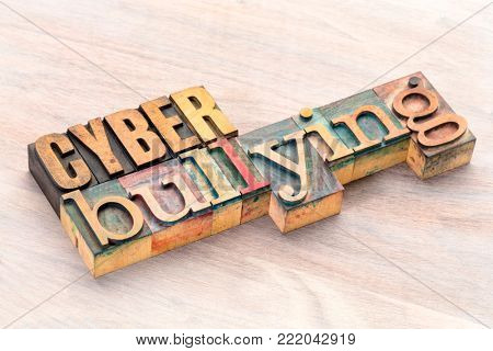 cyber bullying word abstract- text in vintage  letterpress wood type printing blocks stained by color inks