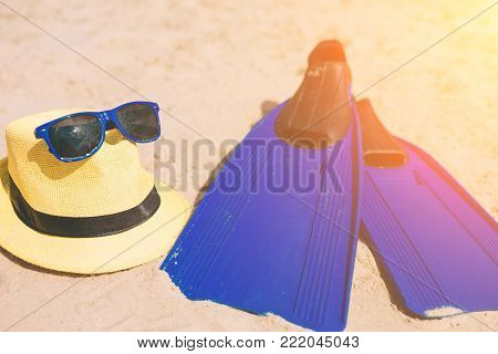 Swim flippers hat and sunglasses on the sandy beach