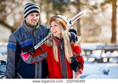 Young couple bring skis on shoulder on winter holiday