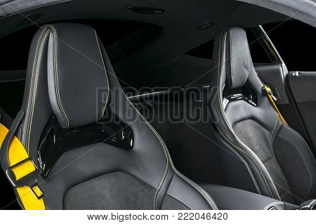 Modern Luxury sport car inside. Interior of prestige modern car. Comfortable leather seats with yellow stitching. Black perforated leather. Modern car interior details. Yellow seat belt lock