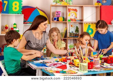 Children painting craft lesson in primary school. Harm of raising boys in women's team. Kindergarten teacher and small students work together. Children with teacher are preparing for art exhibition.