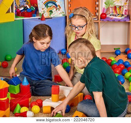 Children building blocks in kindergarten. Group kids playing toy on floor. Interior preschool. Kid is keen on playing dice. Game of block replaces games on smartphone.