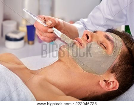 Mud facial mask of man in spa salon. Massage with clay full face in therapy room. Man lying on spa bed. Beautician hand therapeutic procedure background. Anti-aging cosmetic mask.