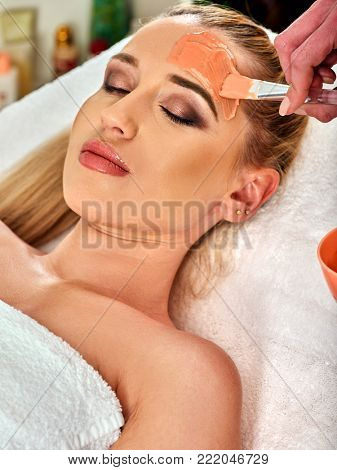 Collagen face mask. Facial skin treatment. Woman receiving cosmetic procedure . Bottle with moisturizing cream on background. Mask against mature skin and black dots.