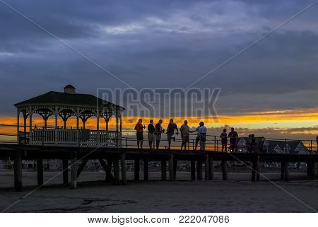 BELMAR, NEW JERSEY - SEPTEMBER 3 - A group of men converse at sunset on the old Belmar fishing pier destroyed during Hurricane Sandy on September 3 2010 in Belmar New Jersey