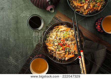 Stir fried at wok noodles with chicken and vegetables in a plate over dark background, top view