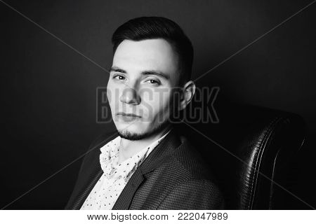 Portrait of a successful young businessman in a business suit and white shirt on a black leather chair. Stylish man. Director of the firm
