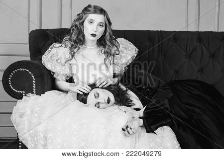 Two girls with long hair in retro dress in the bedroom. Black and white art monochrome photography. Black and white creative photography. Black and white conceptual image. Beautiful black and white background. Black and white portrait.