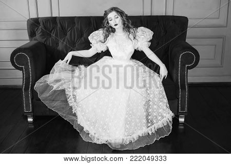 Black and white art monochrome photography. Black and white creative photography. Black and white conceptual image. Beautiful black and white background. Black and white portrait. Woman with long curly hair in a white vintage wedding dress