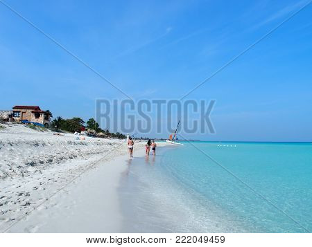 Family on sandy beach at Caribbean Sea in VARADERO city in CUBA with clear water on seaside landscape and exotic palms and trees, clear blue sky in 2017 warm sunny spring day, North America on March.