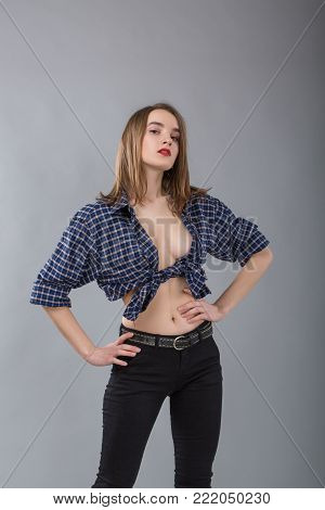Portrait of stylish girl in a cowboy shirt without a bra on a grey background. Cowboy style. model tests
