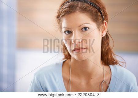Portrait of tired young woman looking at camera