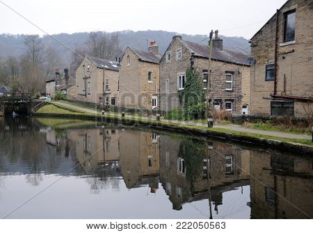houses alongside the rochdale canal in hebden bridge with reflections in the water and lock gates in the distance