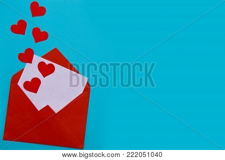 Red envelope with love letter above blue background with many hearts around. Hearts pours out of the envelope. Hearts fly out from the envelope. Love Letter. Love concept