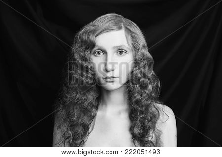 Black and white art monochrome photography. Black and white creative photography. Black and white conceptual image. Beautiful black and white background. Black and white portrait. Woman with long curly flowing hair on a black background.