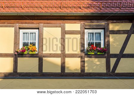 Half-timbered house with window and colorful flowers in Germany. Sunlight and shadow on the wall.