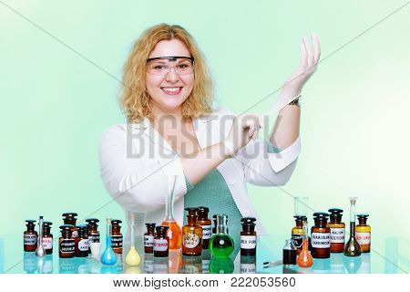 chemist woman or girl student or female laboratory assistant or scientific researcher with chemical glassware test flask. Experiment, research in progress, green background