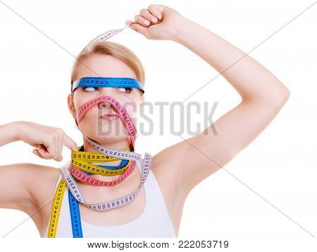 Time for diet slimming weight loss concept. Health care healthy lifestyle. Sport fit fitness woman with a lot of colorful measure tapes around her head. Obsessed girl by your body.  isolated on white background