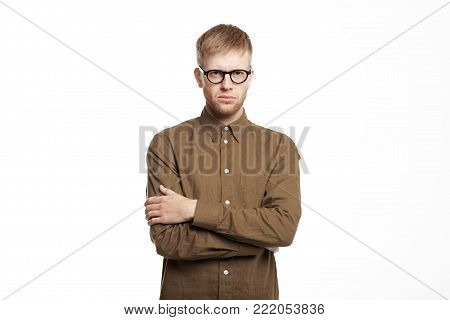 Attractive confident young European man with stubble crossing arms on his chest, having serious distrustful look, posing in closed posture which means his dislike, discontent or stubbornness