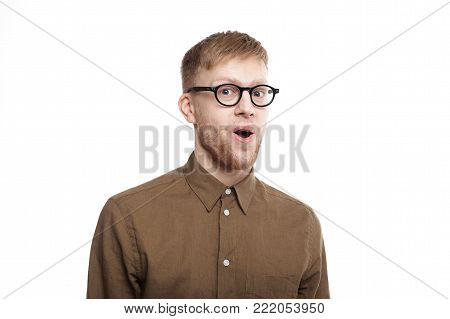 Wow. Studio shot of handsome emotional hipster guy in stylish eyewear staring at camera in full disbelief, raising brows and opening mouth, having completely shocked expression on his hairy face