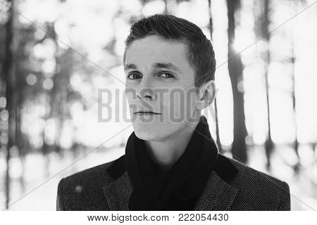 Black and white art monochrome photography. Black and white creative photography. Black and white conceptual image. Beautiful black and white background. Black and white portrait.Young attractive man with short hair wearing a gray winter coat