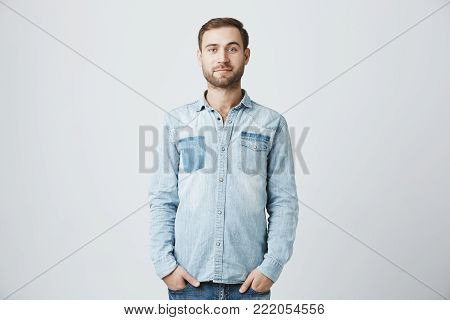 Good-looking attractive young bearded entrepreneur with stylish haircut dressed in denim shirt posing indoors, holding his hands in pockets. Isolated shot, horizontal