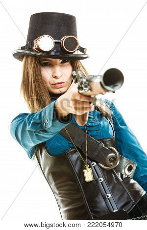 Young steampunk islolated girl on white wearing fancy hat. Fantasy old fashion with stylish topper goggle and gun aiming.