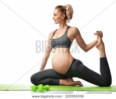 Pregnant woman doing sport stretching exercises green weights. Pregnancy motherhood expectation healthy life and weight control concept isolated on a white background