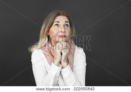 Candid shot of religious blonde Caucasian middle aged woman clasping hands and looking up, praying, asking for forgiveness, her look expressing regret. Religion, prayer, pleading and begging concept