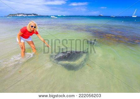 Happy blonde woman pointing at big Australian Eagle Ray close to shore in Hamelin Bay, Margaret River Region, Western Australia. Female tourist enjoys eagle sting rays popular attraction in this place